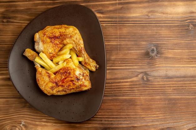 Vista de cima em close-up prato de fast food com batatas fritas e coxas de frango no lado esquerdo da mesa de madeira