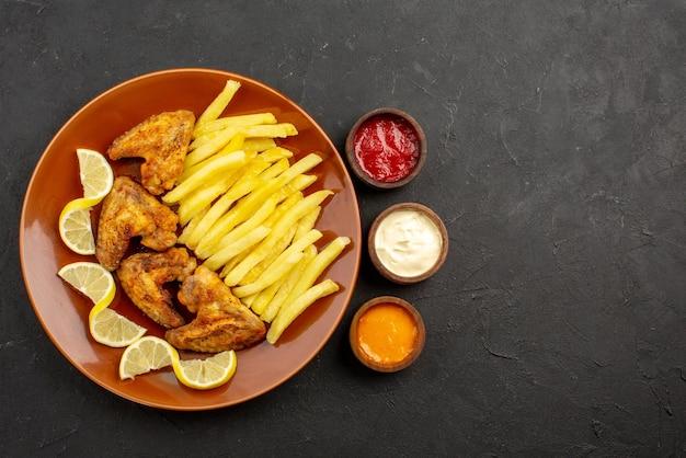 Vista de cima em close-up prato de fastfood com asas de frango, batata frita e limão, e tigelas com três tipos de molhos no lado esquerdo da mesa escura