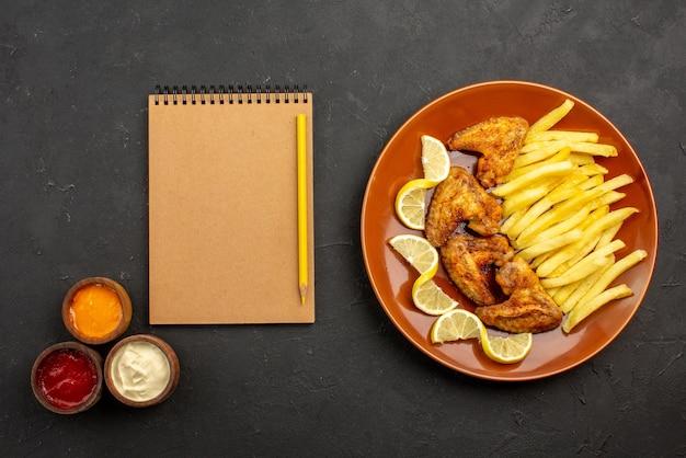 Vista de cima em close-up prato de fastfood de apetitosas batatas fritas com asas de frango e limão à direita e três tipos de molhos ao lado do caderno e lápis do lado esquerdo da mesa
