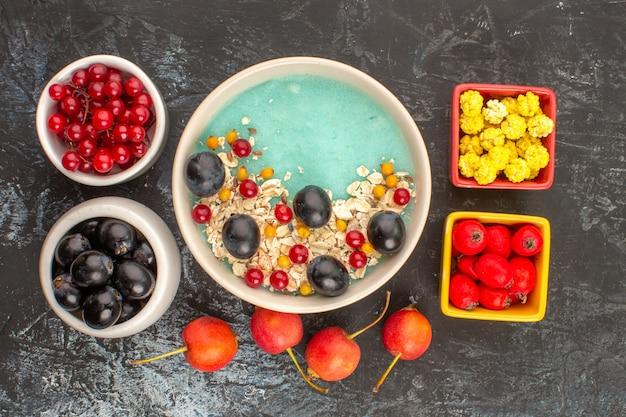Vista de cima em close-up prato de frutas vermelhas de aveia e frutas tigelas de doces de uvas vermelhas