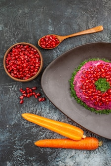 Vista de cima em close-up prato de romãs tigela de sementes de romã ervas cenouras