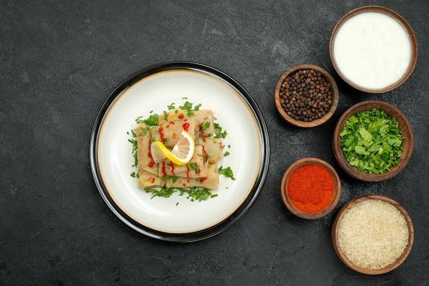 Vista de cima em close-up prato e especiarias recheado de repolho com molho de limão e ervas e tigelas de especiarias coloridas, ervas, creme azedo, arroz e pimenta preta na mesa de madeira