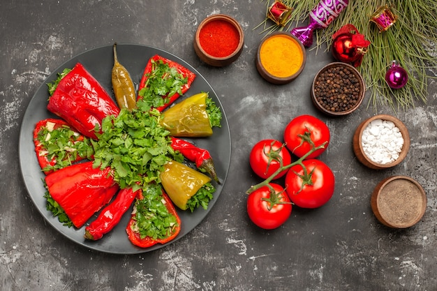 Vista de cima em close-up prato pimentas com ervas, tomates e especiarias penicels, brinquedos para a árvore de natal