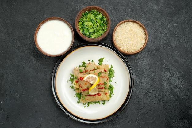 Vista de cima em close-up prato repolho recheado com ervas limão e molho no prato e tigelas com ervas, arroz e creme de leite no centro da mesa preta
