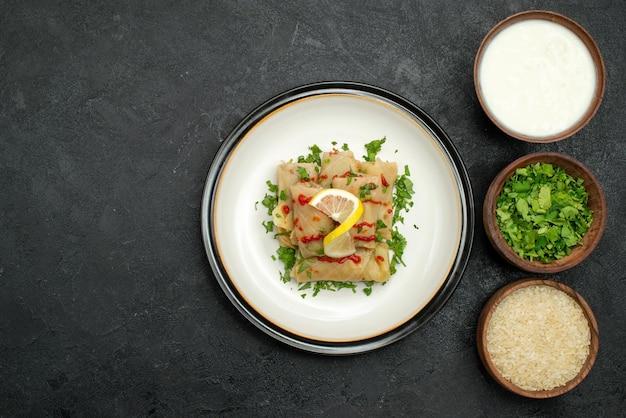 Vista de cima em close-up prato saboroso repolho recheado com ervas limão e molho no prato branco e arroz com ervas e creme de leite em pratos do lado direito da mesa preta