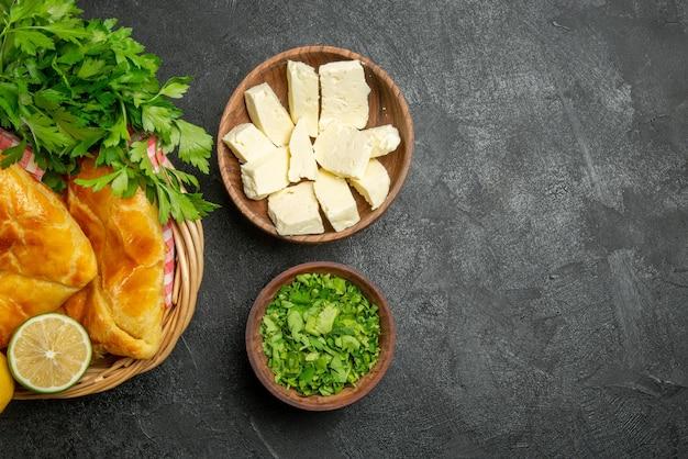 Vista de cima, em close-up, queijo, ervas, tortas apetitosas, limão e ervas e toalha de mesa quadriculada na cesta de madeira e tigelas de ervas e queijo