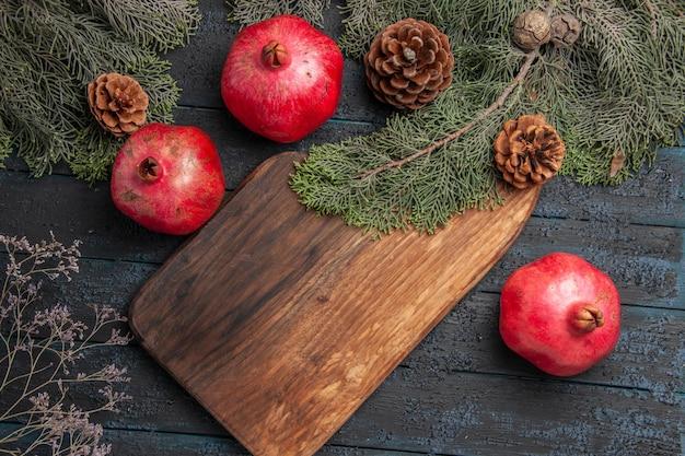 Vista de cima em close-up ramos e romãs apetitosas romãs vermelhas ao lado da tábua de cortar duas romãs e ramos com cones na superfície cinza