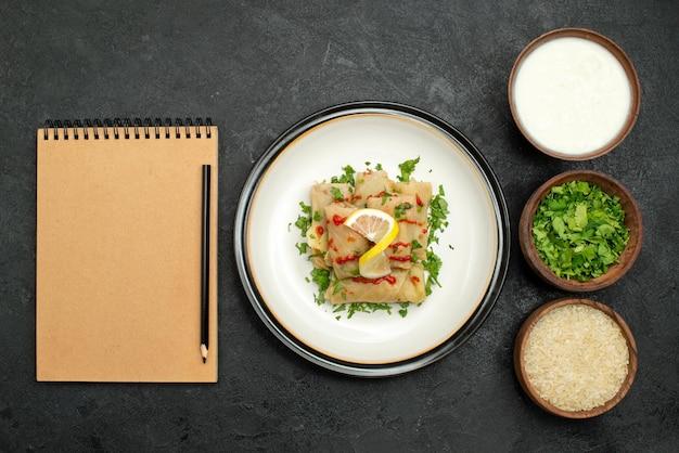 Vista de cima, em close-up, repolho recheado, repolho recheado, com ervas, limão e molho no prato branco e arroz com ervas e creme de leite em pratos ao lado do caderno de creme e lápis na mesa preta