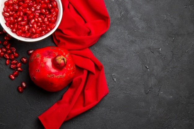Vista de cima em close-up romã romã ao lado das sementes de romã na tigela toalha de mesa vermelha