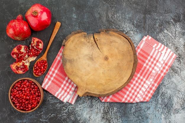 Vista de cima em close-up romã romã na tigela a tábua de corte na toalha de mesa quadriculada