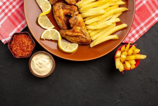 Vista de cima em close-up saborosa galinha apetitosa asas de frango batatas fritas e tigelas de limão com diferentes tipos de molhos e especiarias no centro da mesa escura