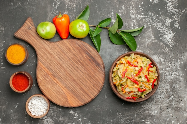Vista de cima em close-up saladeira com salada de pimentões e especiarias com folhas ao lado do tabuleiro