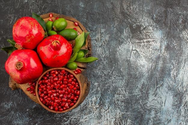 Vista de cima em close-up sementes de romãs de romã em uma tigela três romãs na mesa da cozinha