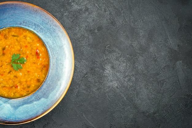 Vista de cima em close-up sopa uma sopa apetitosa com ervas na tigela sobre a mesa