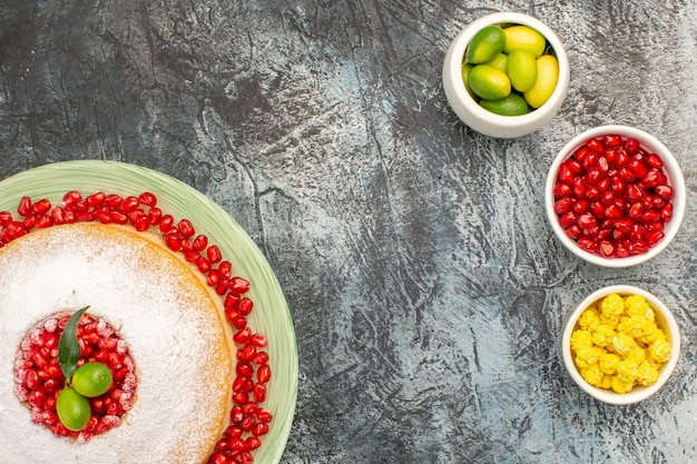 Vista de cima em close-up taças de bolo de doces e frutas cítricas de romã no prato de um bolo apetitoso