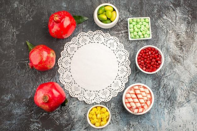 Vista de cima em close-up taças de doces com doces coloridos e frutas cítricas de romã em volta do guardanapo de renda