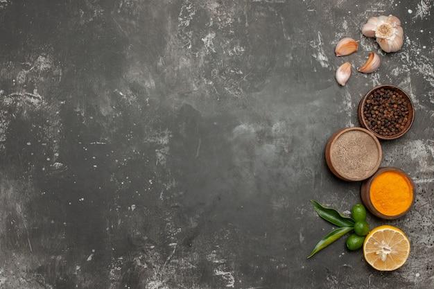 Vista de cima em close-up taças de especiarias, frutas cítricas e alho