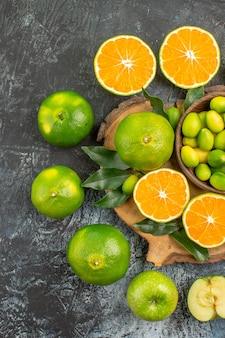 Vista de cima em close-up, tangerinas de frutas cítricas em volta da tábua de corte com frutas cítricas