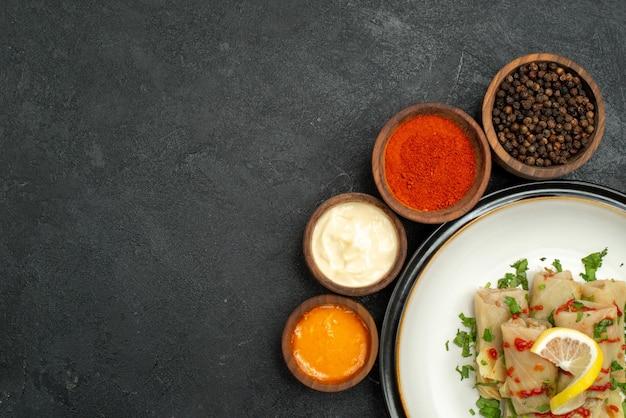 Vista de cima em close-up temperos e molhos tigelas de arroz molho amarelo ervas de creme azedo pimenta preta e temperos coloridos ao redor do prato branco de repolho recheado no lado direito da superfície escura
