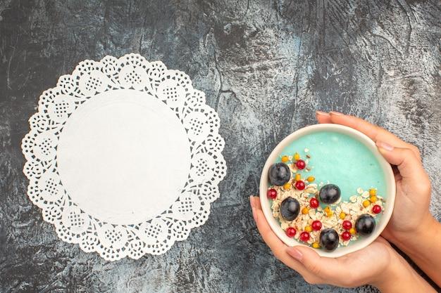 Vista de cima em close-up tigela de bagas de aveia com frutas coloridas no guardanapo de renda de mãos