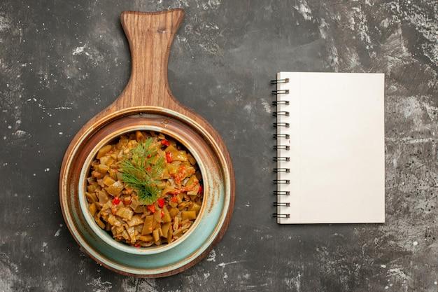 Vista de cima em close-up tigela de feijão verde com apetitosos tomates feijão verde na mesa da cozinha ao lado do caderno branco sobre o fundo preto