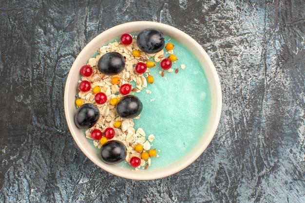 Vista de cima em close-up tigela de frutas com apetitosas groselhas e uvas na mesa cinza