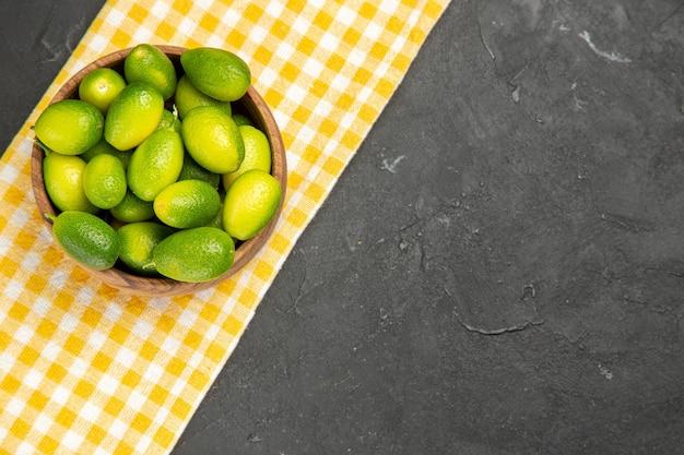 Vista de cima em close-up tigela de frutas com frutas na toalha de mesa branco-amarela na mesa escura