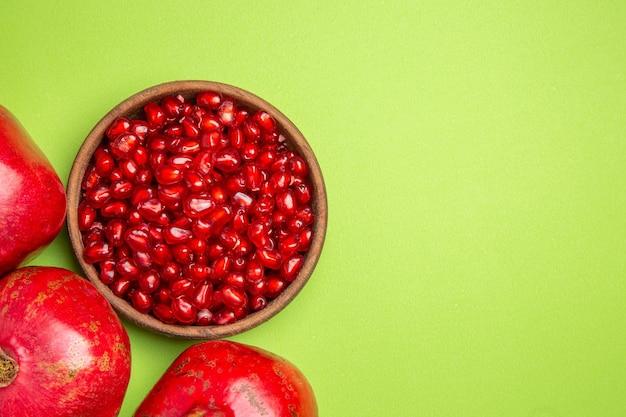 Vista de cima em close-up tigela de frutas com sementes de romã na mesa verde