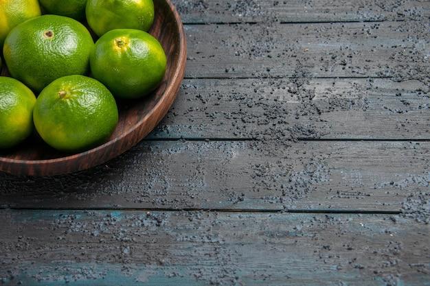 Vista de cima em close-up tigela de limão verde-amarelo na mesa cinza