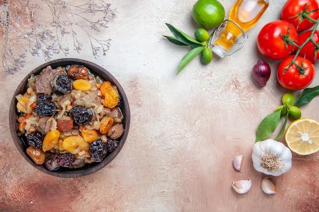 Vista de cima em close-up tigela de pilaf de pilaf com frutas secas, tomate, alho, óleo, folhas de limão