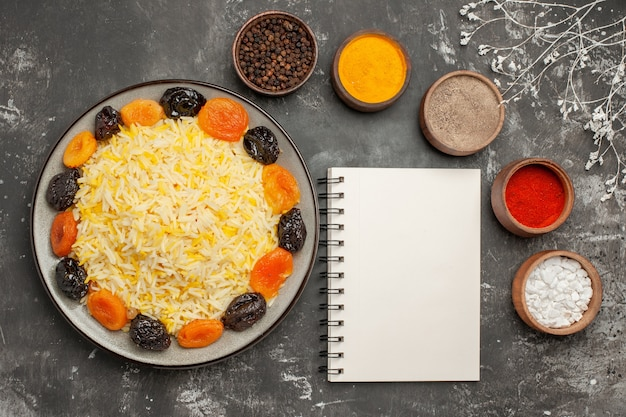 Vista de cima em close-up tigelas de arroz com prato de especiarias coloridas de arroz e caderno branco