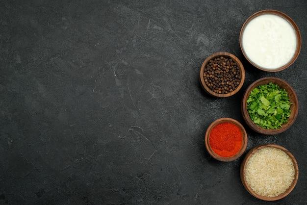 Vista de cima, em close-up, tigelas de especiarias coloridas de ervas de especiarias coloridas, pimenta preta, creme de leite e arroz no lado direito da mesa cinza