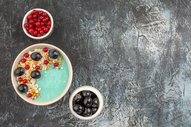 Vista de cima, em close-up, tigelas de frutas das frutas e uvas apetitosas na mesa cinza