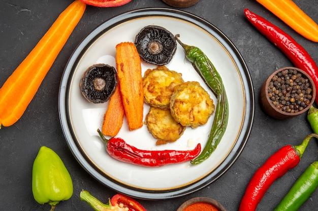 Vista de cima em close-up tigelas de legumes com especiarias, cenoura, pimenta, legumes assados