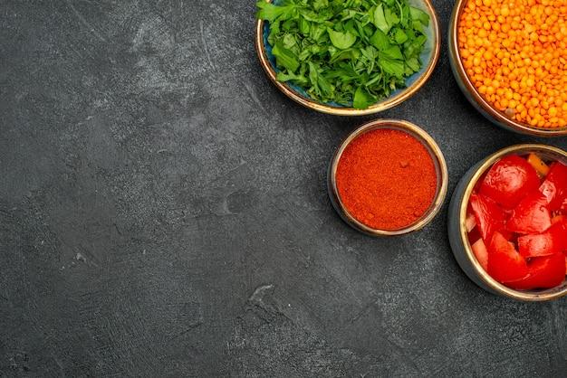 Vista de cima em close-up tigelas de lentilha com especiarias e ervas de lentilha e tomate