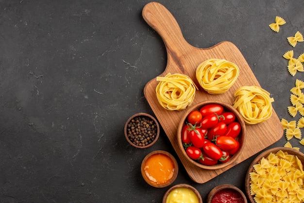 Vista de cima em close-up tomates e tigelas de macarrão com diferentes molhos e temperos ao lado da tigela de tomates e macarrão na tábua de corte sobre a mesa
