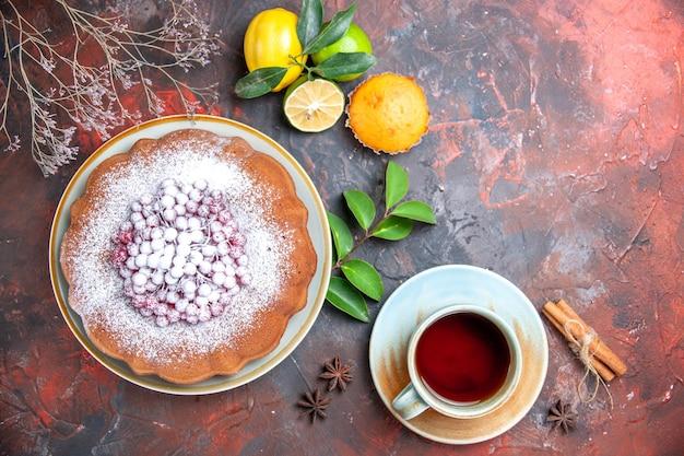Vista de cima em close-up um bolo com açúcar cítrico em pó, canela, anis estrelado, uma xícara de chá