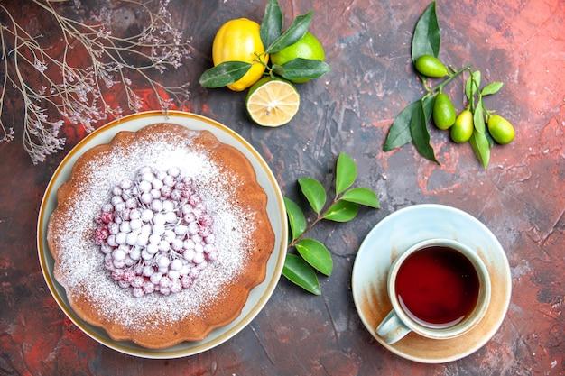 Vista de cima em close-up um bolo com frutas cítricas com açúcar em pó e folhas uma xícara de chá