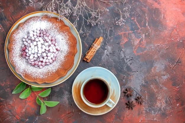 Vista de cima em close-up um bolo um bolo com açúcar de confeiteiro anis estrelado e canela uma xícara de chá