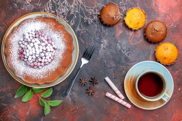 Vista de cima em close-up um bolo um bolo com anis estrelado quatro cupcakes uma xícara de chá
