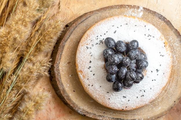 Vista de cima em close-up um bolo um bolo com espigas de uvas pretas na mesa