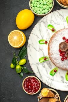 Vista de cima em close-up um bolo um bolo com frutas cítricas geléia biscoitos doces verdes