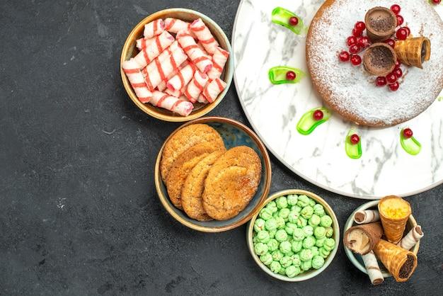 Vista de cima em close-up um bolo um bolo com waffles de frutas e tigelas de biscoitos doces coloridos