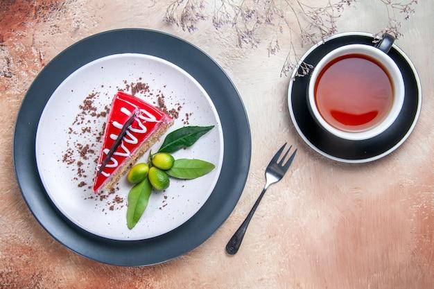 Vista de cima em close-up um prato de bolo com molho de chocolate frutas cítricas garfo uma xícara de chá