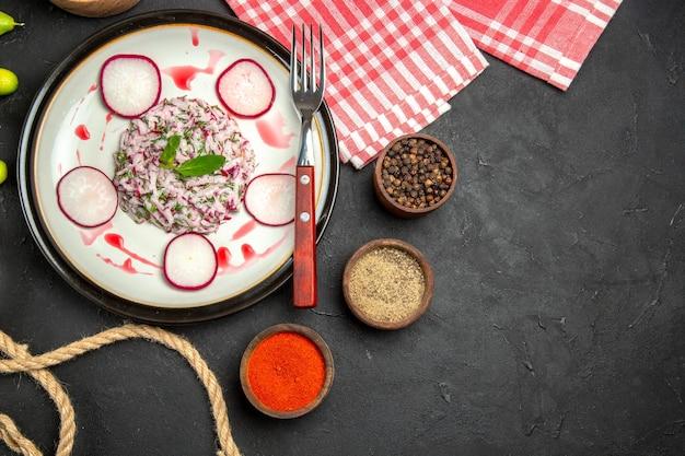 Vista de cima, em close-up, um prato de prato com tigelas de garfo avermelhado de especiarias e a toalha de mesa quadriculada