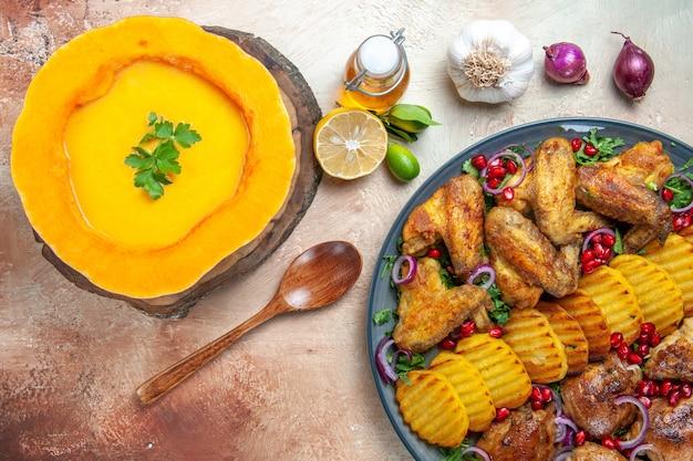 Vista de cima em close-up um prato de sopa de canja de galinha e abóbora no quadro colher óleo cebola e limão