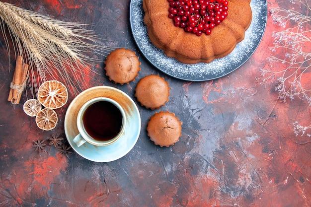 Vista de cima em close-up uma xícara de bolo de chá com bolinhos de frutas vermelhas uma xícara de chá doces em pau de canela