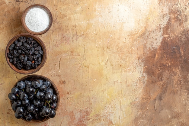 Vista de cima em close-up uvas uvas pretas açúcar passas em tigelas de marrom