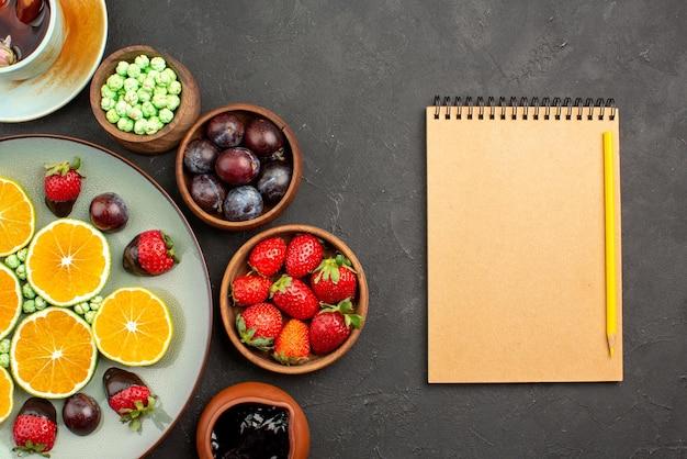 Vista de cima em close-up xícara de chá e frutas uma xícara de chá com cobertura de chocolate, morango picado de laranja e balas verdes e tigelas com diferentes frutas e doces ao lado do caderno e lápis