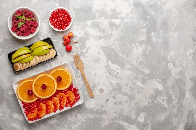 Vista de cima em fatias de laranjas com framboesas em um fundo claro.